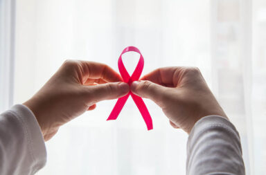 hands-holding-pink-ribbon-with-white-background